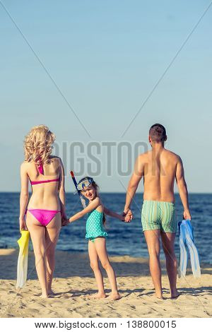 Back view of young parents and their little daughter in swimsuits holding hands standing on the sunny beach. Couple is holding swim fins. Girl is looking at camera
