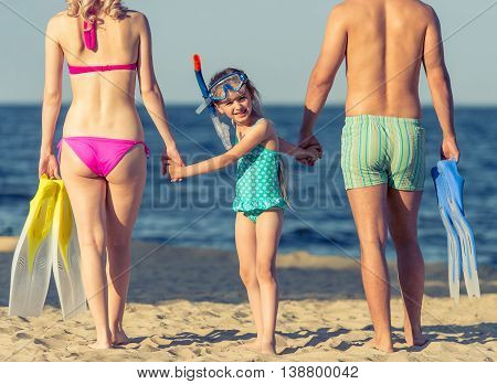 Young parents and their little daughter in swimsuits are holding hands standing on the sunny beach. Girl is looking at camera. Couple is holding swim fins cropped