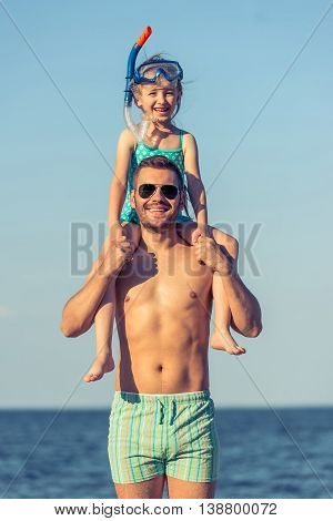 Portrait of handsome young dad and his little daughter looking at camera and smiling sunny beach in the background. Girl is on father's shoulders