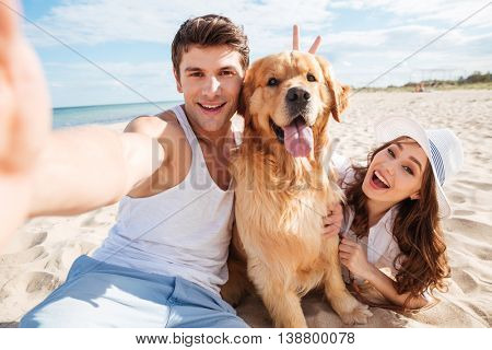 Young happy couple with dog taking a selfie at the beach