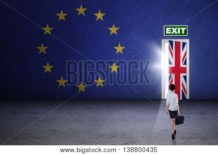 Brexit concept. Female worker carrying a briefcase and walking toward exit door with flag of UK and EU