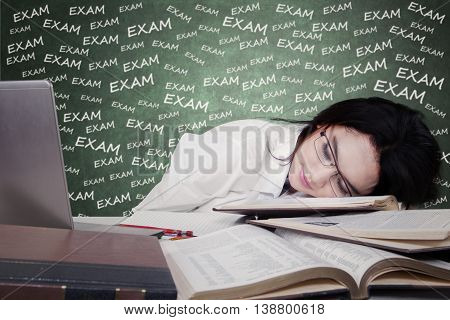 Portrait of beautiful teenage student sleeping above textbooks on desk after studying for exam