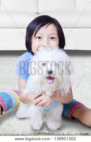 Portrait of little girl smiling at the camera while hugging a maltese dog at home