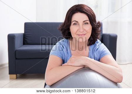 Portrait Of Sporty Mature Woman With Fitness Ball At Home