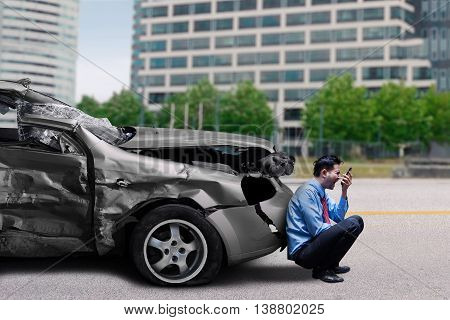 Angry man speaking on the mobile phone while sitting in front of a broken car after traffic accident