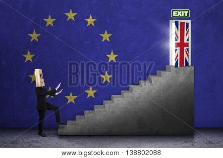 Brexit concept. Businessperson with cardboard head walking on the ladder toward exit door with flag of England and EU