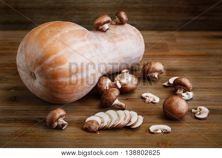 Orange Big Pumkin, Fresh Cut Mushrooms on the Wooden Table.Autumn Garden's Vegetables. Selective Focus