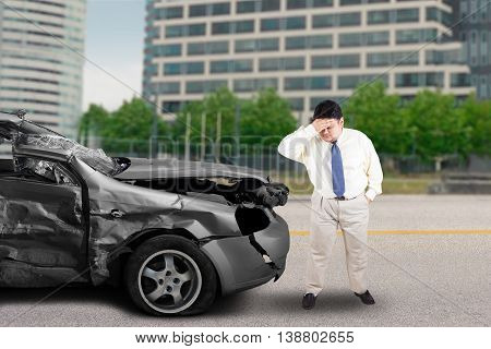 Portrait of stressful businessman standing in front of a broken car after traffic accident on the road