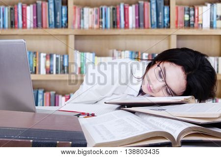 Portrait of teenage schoolgirl sleeping above textbooks and laptop on the table in library