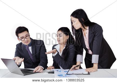 Young female leader looking at the laptop with her two subordinates show the problem