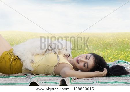 Picture of a beautiful young woman sleeping on the meadow with a maltese dog