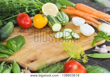 Closeup of fresh locally grown eco organic chopped vegetables on a cutting board on a wooden background. Vegan recipe. Flat lay top view.