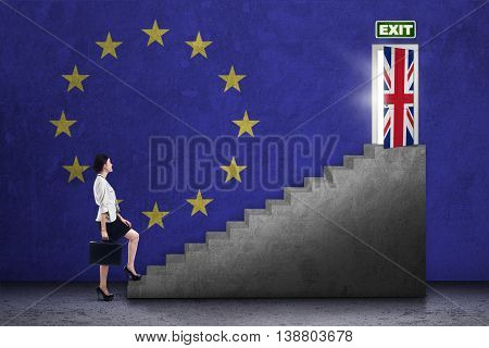 Brexit concept. Young businesswoman walking on the stairs toward exit door with flag of United Kingdom and European Union