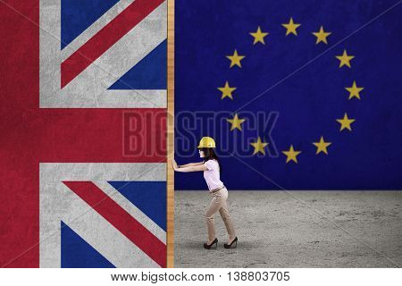 Brexit concept. Female worker wearing helmet and pushing national flag of England with EU flag background