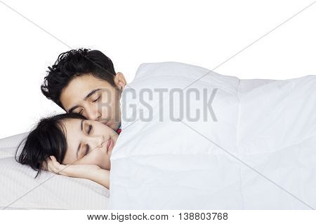 Portrait of young couple sleeping together while a man kissing his wife on the bed