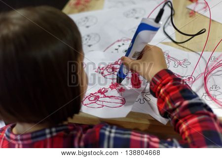 ST. PETERSBURG, RUSSIA - JUNE 28, 2016: Girl drawing with 3D-pen during the interactive exhibition Ball Of Robots. Last year the exhibition was visited by more than 200,000 people in 5 Russian cities