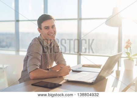 Man using laptop on his workplace. sitting, smiling, looking at camera
