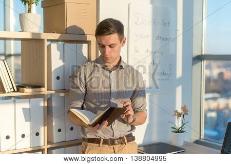 Man working in office, planning work tasks, writing down his schedule to planner at the workplace
