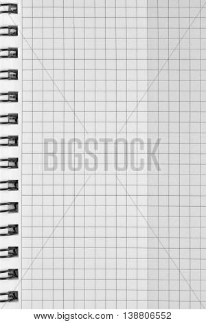 Checked spiral notebook background pattern, vertical chequered squared open notepad copy space, stapled blank empty blocknote reminder concept metaphor, large detailed macro closeup