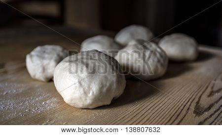 Bread dough balls on a wooden table