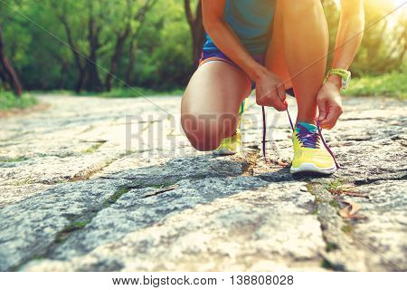 young woman trail runner tying shoelaces on rocky trail in forets
