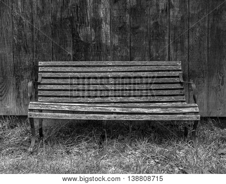 Black and white photo of the weathered lonely bench on the weathered wooden background