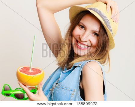 Summer vacation. Happy funny girl tourist in sunglasses and hat holding grapefruit citrus drinking juice from fruit on gray.