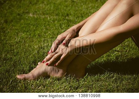 woman barefoot legs on grass side view sunny summer day