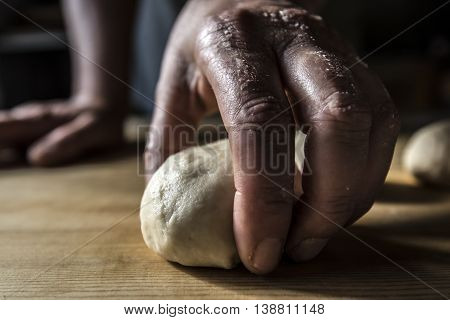 Hands kneading the dough on a wooden table close up