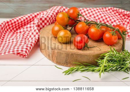 Organic cherry tomatoes with rosemary on rustic wooden table