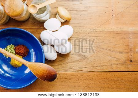 Blue bowl with paprika curry and oregano wooden spoon eggs and dehydrated potato on wooden board