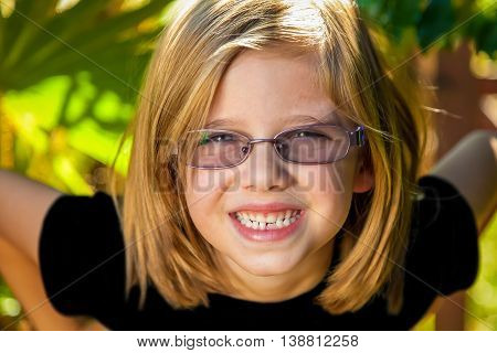 A young girl leans forward with a big smile and her hands on her hips. She is blond and is wearing glasses. Model released.