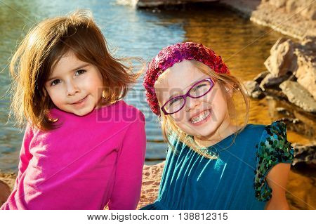 Two young sisters sit at the edge of a lake with heads tilted to the side smiling at the camera. Model releases.