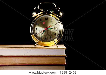 alarm clock standing on old books