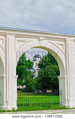 Arcade of the ancient Yaroslav courtyard at summer sunny day in Veliky Novgorod Russia - unusual composition with the St Nicholas Cathedral in one of the arches. Architecture landscape
