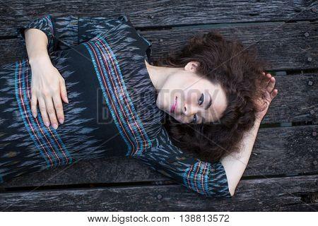 Beautiful Asian girl lying on a wooden podium.