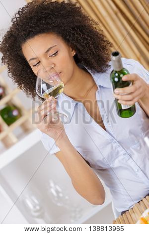 attractive woman tasting wine while sitting in restaurant