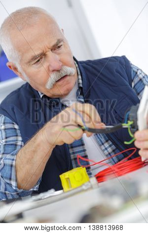 casual senior electrician at work