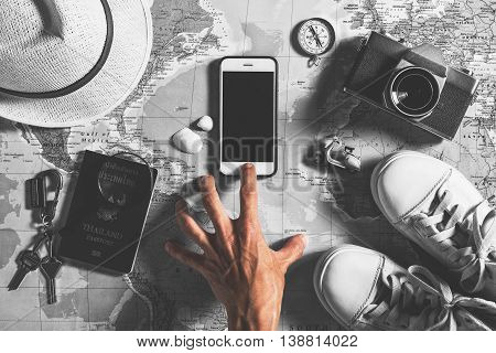 Travel concept The hand of traveler push on a smart phone Traveler accessories with passport shoe camera hat compass keys magnifier and smart phone