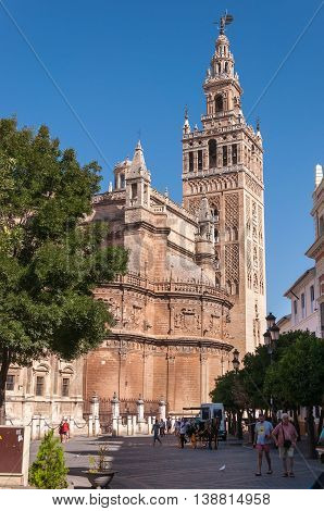 Seville Spain - August 28 2014: Southeastern side of the Seville Cathedral with its bell tower Giralda.