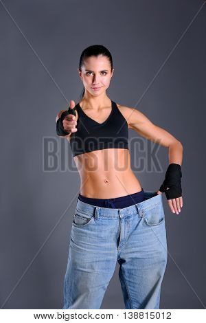 Young fitness woman showing that her old jeans and showing ok.