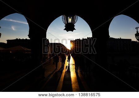Tourists on the main market square in Cracow. View at sunset from the Cloth Hall, Polish Sukiennice.