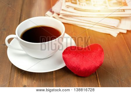 Coffee cup and heart with newspaper in background on wooden table. Sunlight filter effect photo.