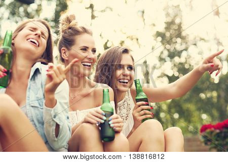 Picture presenting happy group of friends having a beer outdoors