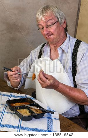 Funny elderly man breaking a tooth while eating his tv dinner