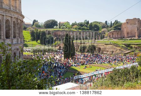 ROME, ITALY - APRIL 8, 2016: Rome's marathon. Ruins of Coliseum and lots of people on the square during the sport's event.