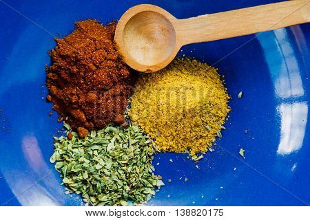 Ceramic bowl with paprika oregano and curry with wooden spoon
