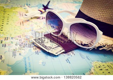 Sunglasses, Passport, Money, Hat And Aircraft On The World Map