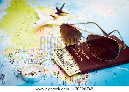 Sunglasses, Passport, Money, Compass And Aircraft On The World Map