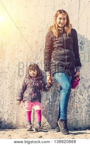 hipter mother and daughter 2 years post same posion with wall behide so lovly family vintage style tone